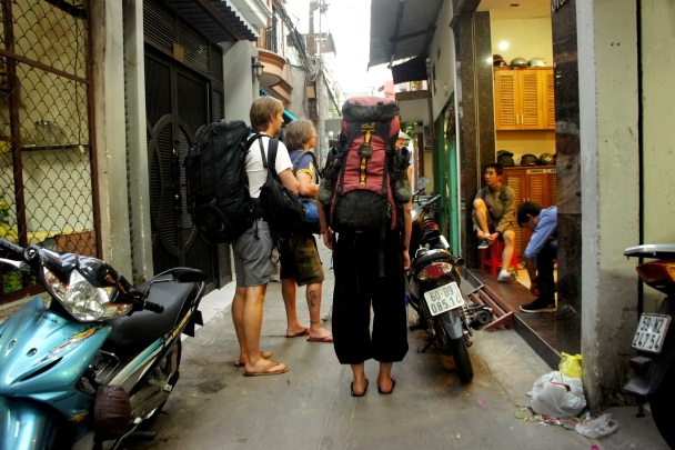 tourists with big backpacks in an alley in vietnam